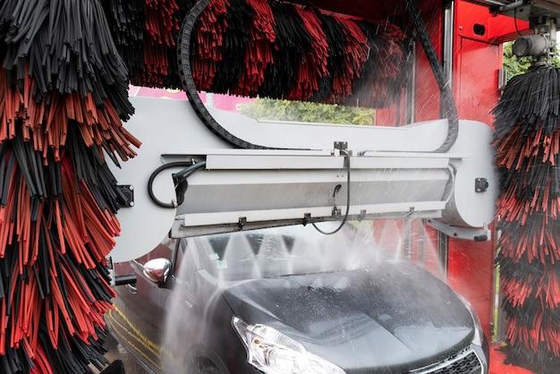 Vista in dettaglio su autolavaggio, acqua schiuma autolavaggio, autolavaggio automatico in azione