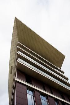Vista di dettaglio della cima di un edificio moderno. design a forma angolare. vista urbana astratta con un cielo. architettura con angolo acuto.