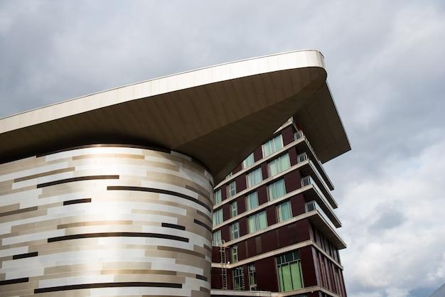 Vista di dettaglio della cima di un edificio moderno. design a forma angolare. pattern con vetrate e linee. architettura con angolo acuto.