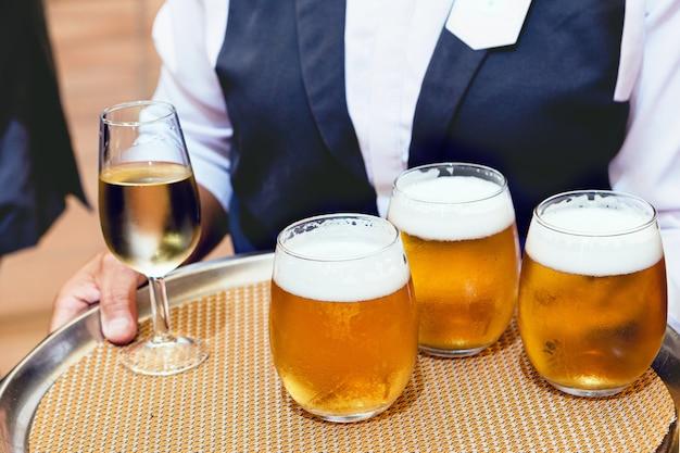 Dettaglio di un cameriere in tuta che serve birra artigianale fredda su un vassoio a una festa in un ristorante