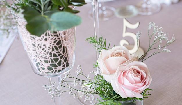 Particolare di una tavola di nozze con bouquet di rose rosa e foglie verdi come decorazione