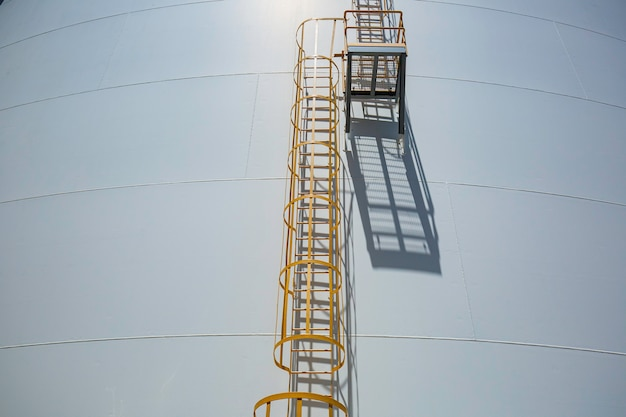 Particolare dei serbatoi bianchi di propano in serbatoio con scaletta in ferro.