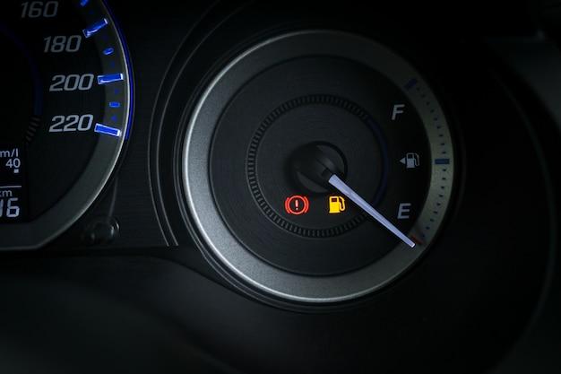 Dettaglio con gli indicatori di livello del carburante che mostrano e serbatoio vuoto sul cruscotto dell'auto