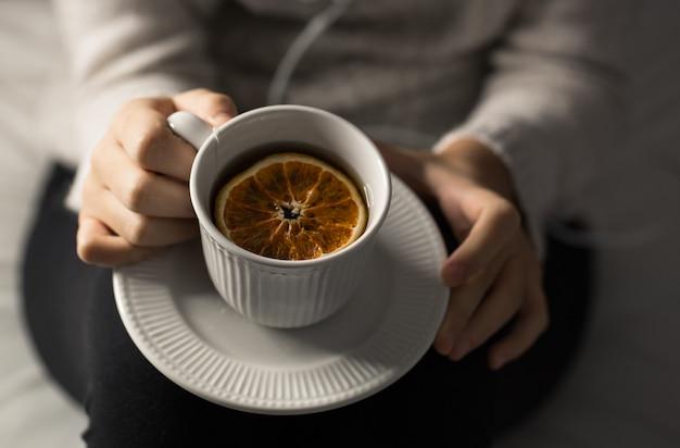 Dettaglio delle mani della donna che tengono una tazza di tè viste dall'alto
