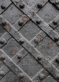Particolare della porta in ferro battuto con un piatto di metallo intrecciato e chiodi scolpiti