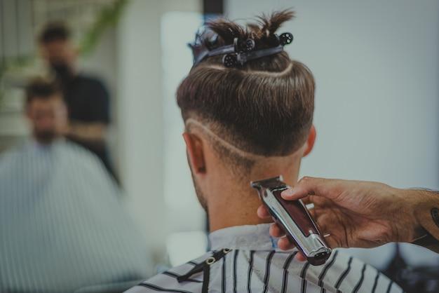 Dettaglio di un giovane che taglia i capelli di un uomo in un barbiere