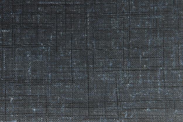 Primo piano dettagliato vintage vecchia tela ruvida tessuto, fondo rustico in nero, grigio. modello macro tela. texture leggera di lino naturale.