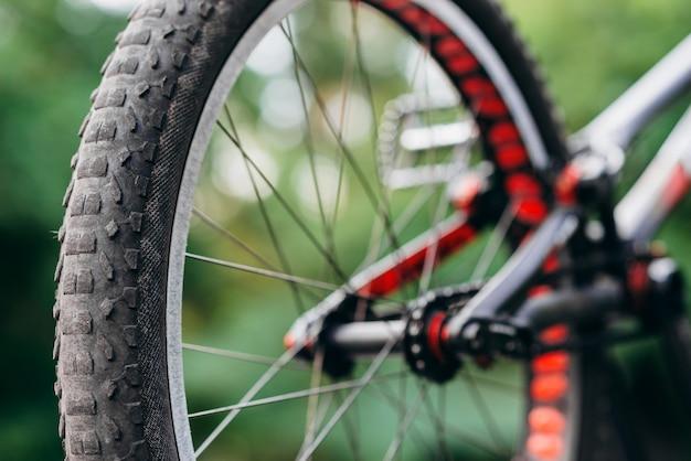 Vista dettagliata dei meccanismi della bicicletta. pignone, pedale e catena su una mountain bike. primo piano della ruota della bicicletta sulla strada