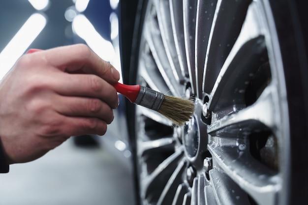 Dettagliare le ruote dell'auto con prodotti chimici per la pulizia. spazzola per la pulizia delle ruote. autochimica per il wetailing.
