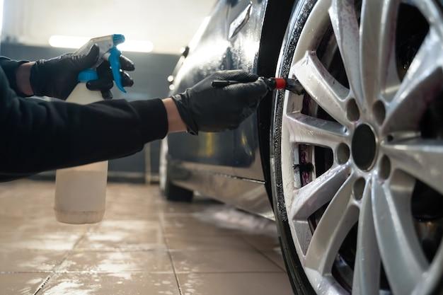 L'operatore del centro di dettagli pulisce le ruote dell'auto con la spazzola.