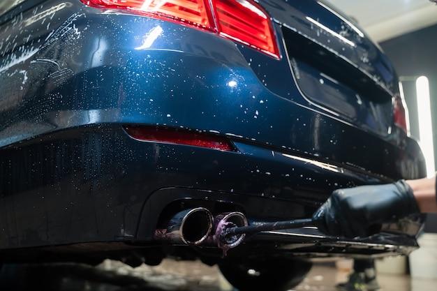 Lavoratore di dettagli pulisce il tubo di scarico dell'auto.