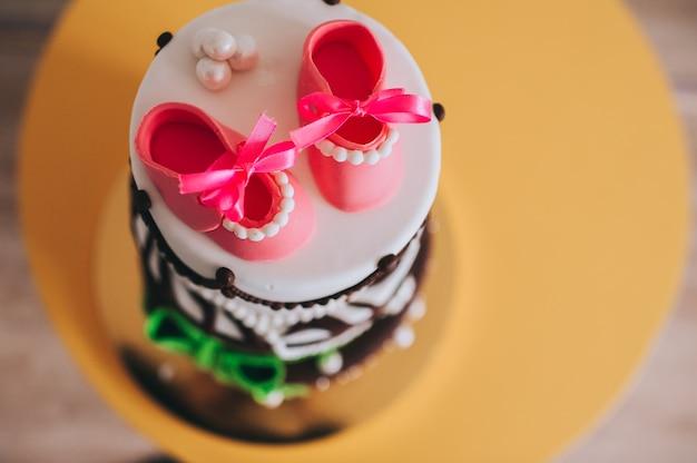 Dettagli di una torta di compleanno per bambina con zucchero dolce scarpe in cima