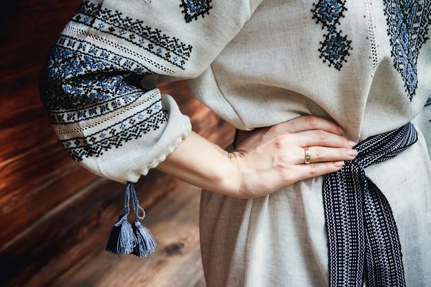 Dettagli della camicia ricamata della sposa sullo sfondo di una casa in legno. dettagli del modello