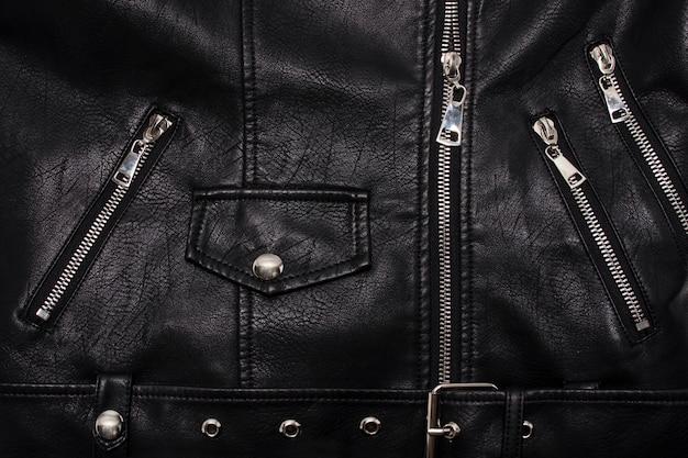 Dettagli di una giacca di pelle con chiusura, rivetti e tasche
