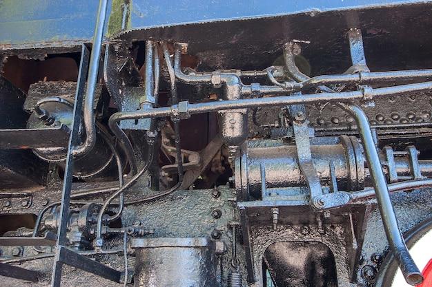 Dettagli e meccanismi con collegamenti da una vecchia locomotiva a vapore. tubi e cilindri, leve. dipinto in nero.
