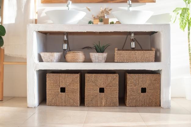 Dettagli del bagno interno bianco accogliente moderno con scatole di vimini