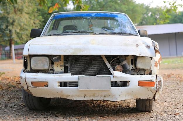 Dettagli di una vecchia automobile arrugginita bianca di incidente