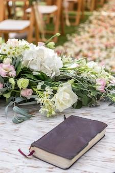 Dettagli di cerimonia nuziale, fiori e petali per la decorazione. bibbia