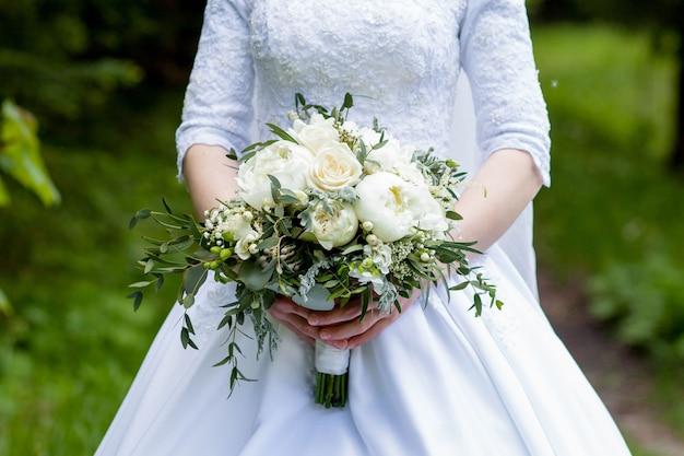 Dettagli della mattina del matrimonio. bouquet da sposa nelle mani della sposa in tenui colori pastello.