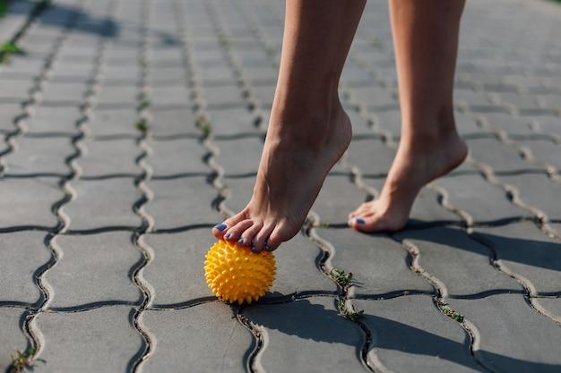 Dettagli della giovane donna a piedi nudi in piedi in punta di piedi su una palla gialla di gomma appuntita per rilassare i muscoli e ridurre il dolore sulla piastrella di pavimentazione in una giornata di sole.