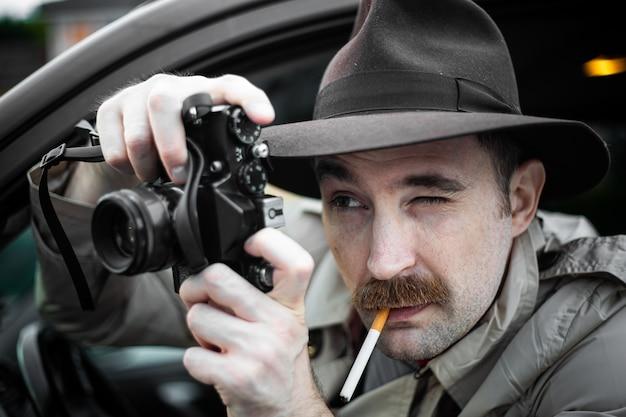 Detective che fuma una sigaretta nella sua macchina mentre spia qualcuno con la sua macchina fotografica