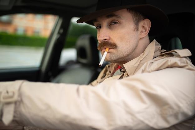 Detective che fuma una sigaretta in macchina