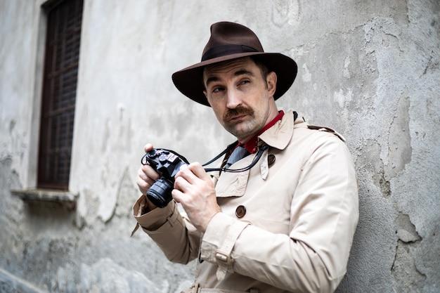 Detective scatta foto in una baraccopoli con la sua macchina fotografica vintage