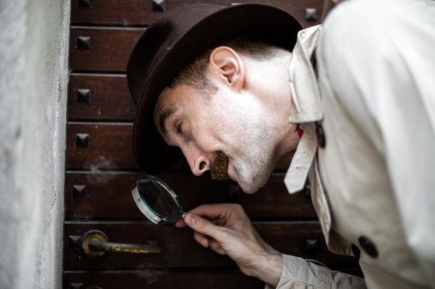 Detective usando una lente di ingrandimento