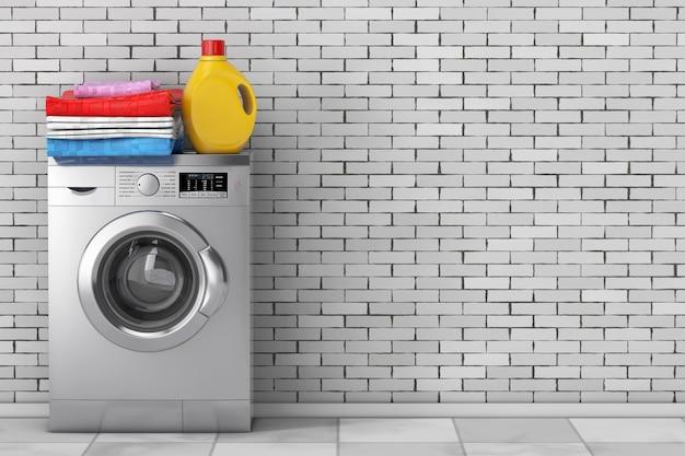 Bottiglia di detersivo e mucchio di vestiti sopra la moderna lavatrice d'argento davanti al muro di mattoni. rendering 3d
