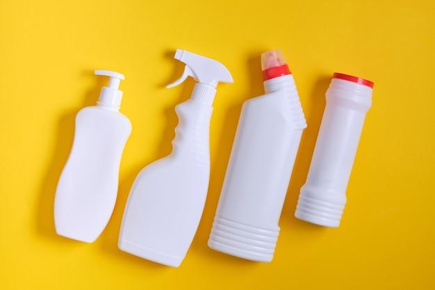 Bottiglie di detersivo su sfondo giallo. forniture per la pulizia chimica