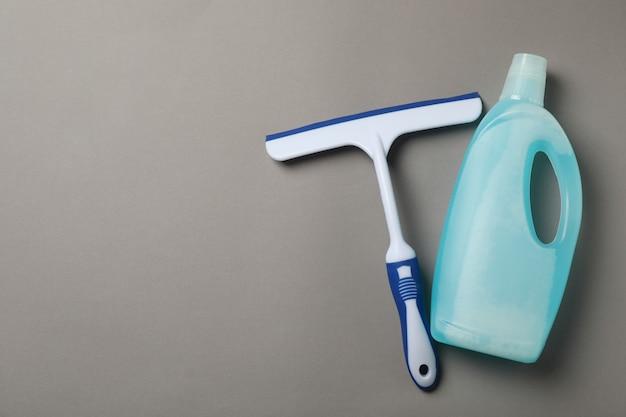 Tergivetro detergente e lavavetri su sfondo grigio