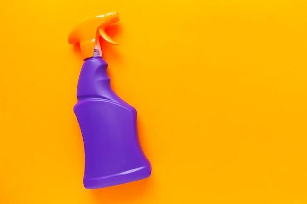 Agente detergente e prodotti per la pulizia, sfondo arancione.