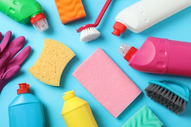 Detersivi e prodotti per la pulizia su sfondo blu, vista dall'alto