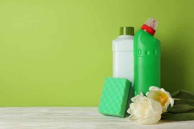 Detergenti, spugna e tulipani sul verde