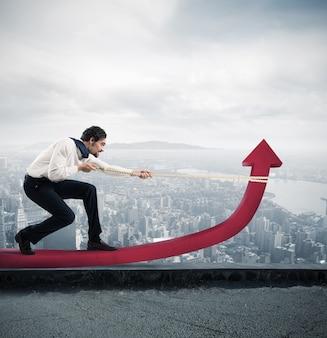 Determinato uomo d'affari con molto sforzo solleva la freccia delle statistiche con una corda sul tetto di un grattacielo