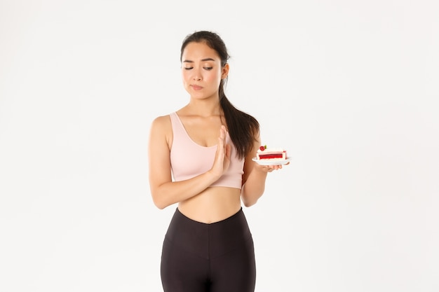Determinato atleta ragazza asiatica che rifiuta i dolci, smette di mangiare cibo spazzatura durante la dieta, perde peso, rifiuta di mangiare la torta, sfondo bianco riluttante in piedi.