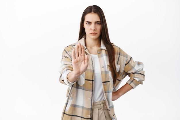 Determinata donna accigliata allunga la mano in stop, blocca il gesto, dice di no, mantiene la distanza sociale durante la pandemia, non avvicinarsi, rifiuta o proibisce qualcosa, non è d'accordo, muro bianco