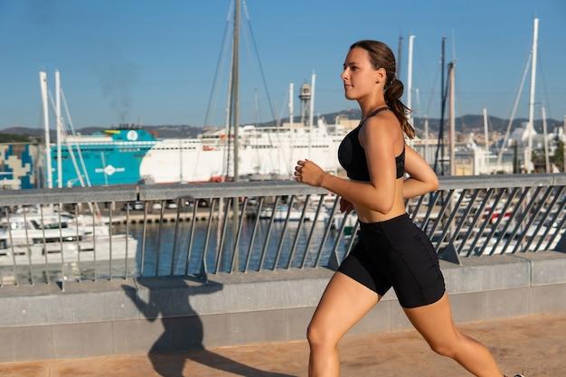 Jogger determinato che corre vicino al porto