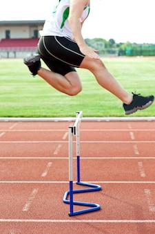 Atleta maschio risoluto che salta sopra la barriera durante la corsa