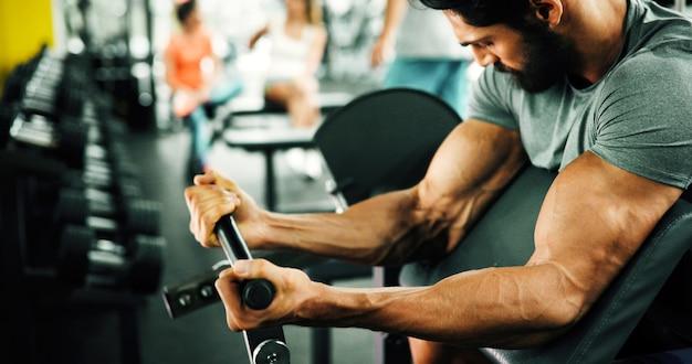 Uomo determinato che si allena in palestra sollevando pesi