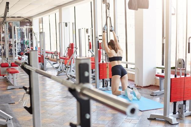 Determinata donna magra dalla schiena in piedi sulle sue ginocchia, con un peso pesante per entrambe le mani, raggiungendo i suoi obiettivi sportivi
