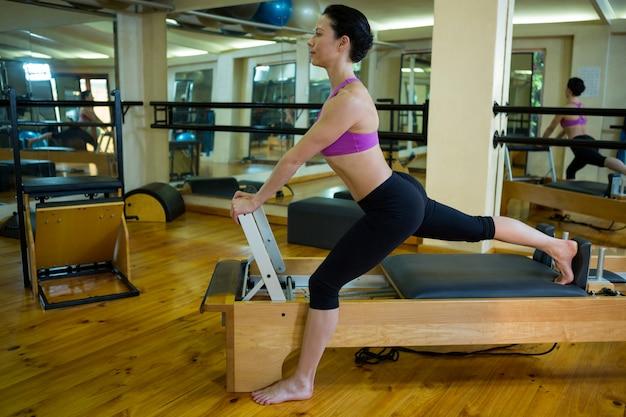 Determinata donna che esegue esercizio di stretching sul riformatore