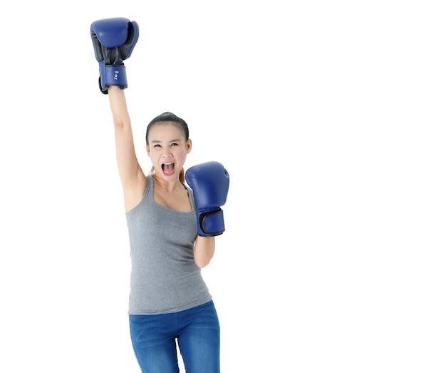 Determinata giovane donna asiatica in abbigliamento casual e guanti da boxe blu alzando la mano e urlando con sfida su sfondo bianco