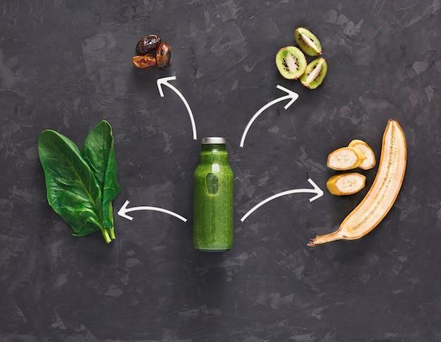Detox cleanse drink concept, frullato di verdure verdi ingredienti. succo sano naturale e biologico in bottiglia per dieta dimagrante o giorno di digiuno. kiwi, banana e mix di spinaci, distesi sul nero