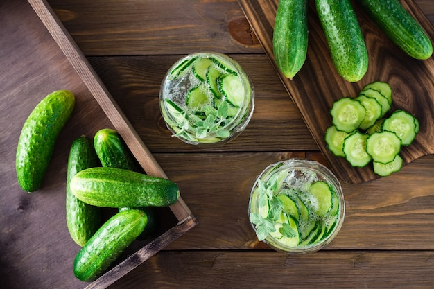 Bevanda disintossicante. acqua con pezzi di cetriolo, ghiaccio e foglie di menta in bicchieri trasparenti su un tavolo di legno. vista dall'alto