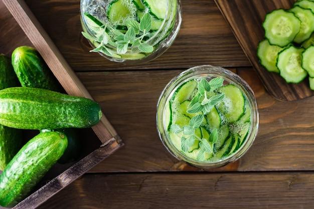 Bevanda disintossicante. acqua con pezzi di cetriolo e ghiaccio in un bicchiere trasparente su un tavolo di legno. vista dall'alto