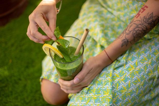 Disintossicante frullato verde per una sana alimentazione nelle mani di una donna
