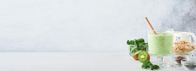 Smoothie verde detox con cavolo riccio, spinaci e kiwi su fondo grigio chiaro di ardesia, pietra o cemento. vista dall'alto con copia spazio.