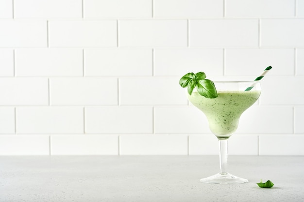 Succo di verdura verde detox o frullato guarnito con foglia di basilico fresco in bicchiere da cocktail su sfondo grigio chiaro di ardesia, pietra o cemento. vista dall'alto con copia spazio.