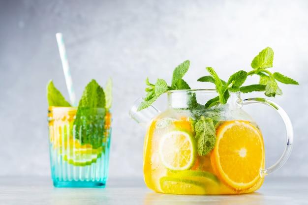 Limonata detox bevanda di acqua, limone, arancia e foglie di menta in una teiera trasparente